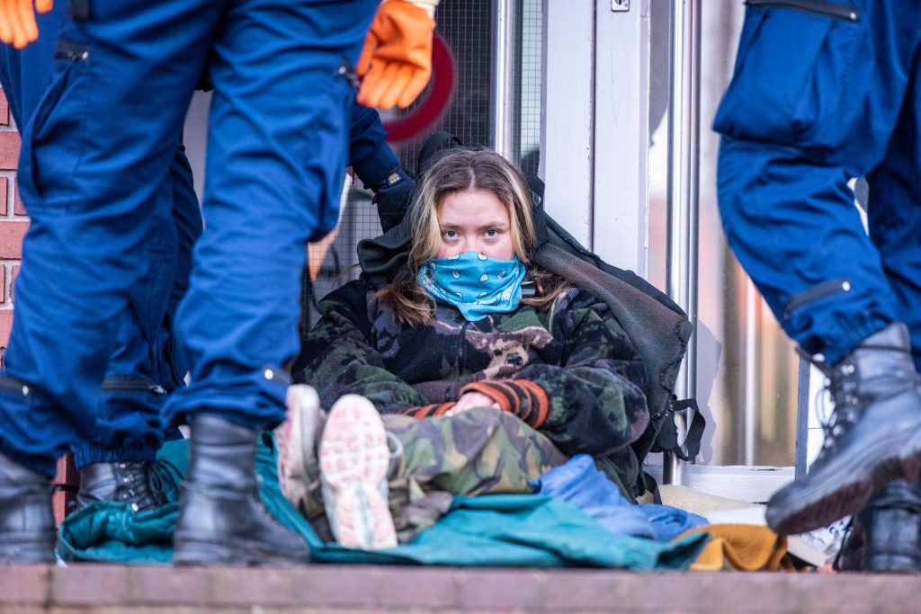 Photo id of a Palestine Action activist sitting against the door of the Elbit weapons factory, dressed up warm and looking determined.