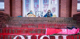 Photo from an action against Elbit Systems showing two protesters sitting in a doorway in front of the weapons factory's graffitied door, which reads 'Shut Elbit Down'. Fake blood is poured across the steps in front of them, as well as a sign that reads 'Ouch'.