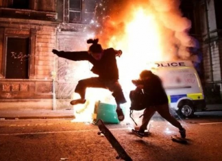 An image of a cop chasing a silhouetted figure, while a police van burns in the background. Keywords; Bristol riot protesters protest peaceful violent police cops
