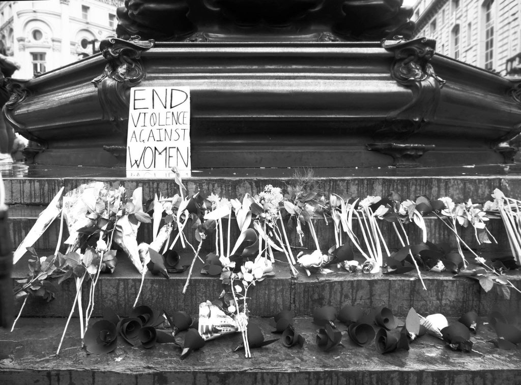 Flowers and a sign reading 'end violence against women'