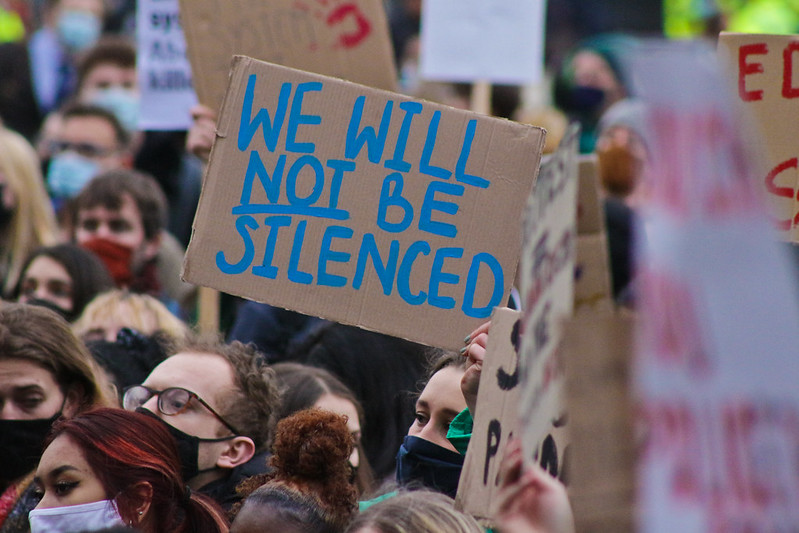 Protesters in London with a placard reading 'We will not be silenced'