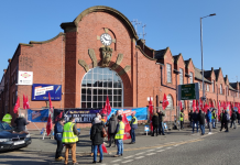 Queen's Road bus garage with pickets and flags