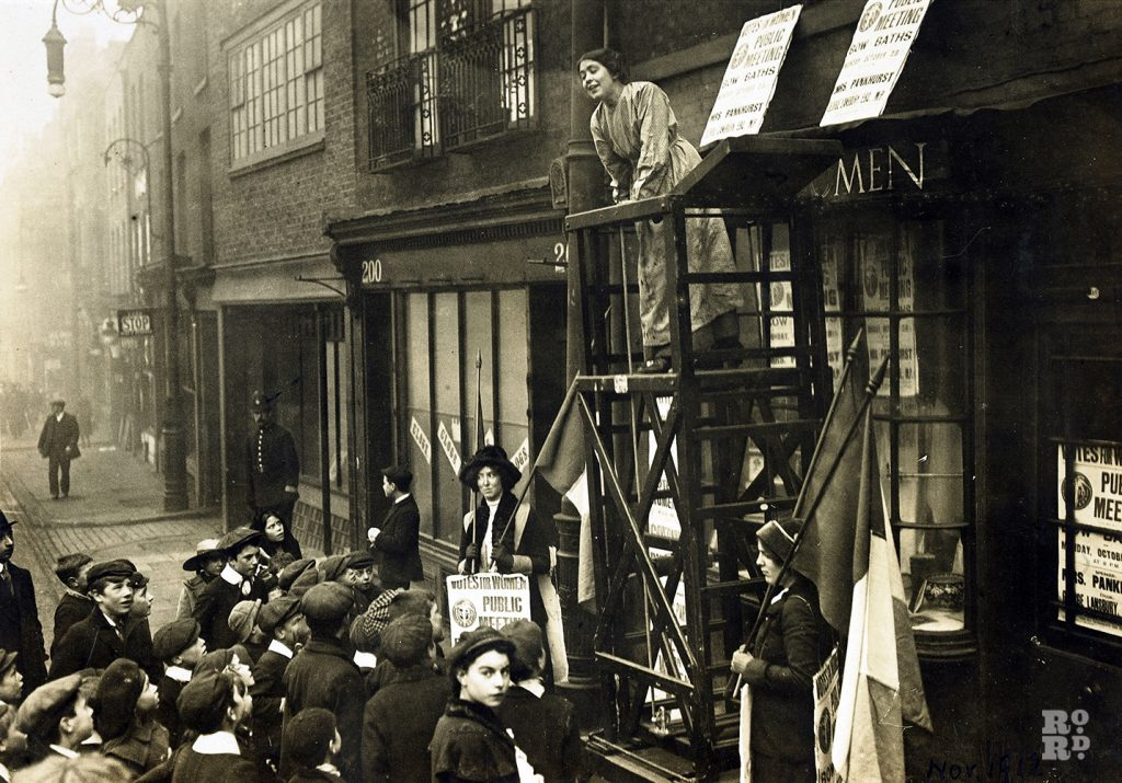 Sylvia Pankhurst addressing a crowd outside the headquarters of the East London Federation of Suffragettes, Old Ford Road, Bow