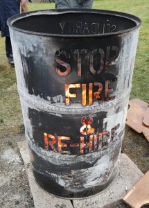 Brazier with flames showing through the cut out words 'Stop fire & re-hire'