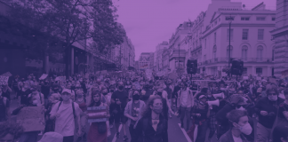 A crowd of people marching through central london at a Black Trans Lives Matter demonstration