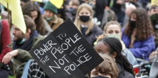 Image shows a woman holding up a placard reading Power to the People Not the Police with a backdrop of other women in the crowd.