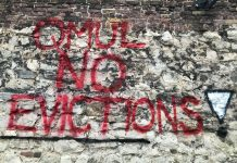 Image shows red graffiti on the wall of a train track reading 'QMUL No Evictions!'