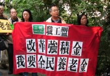 Image shows activists from the Hong Kong Confederation of Trade Unions holding up a flag.