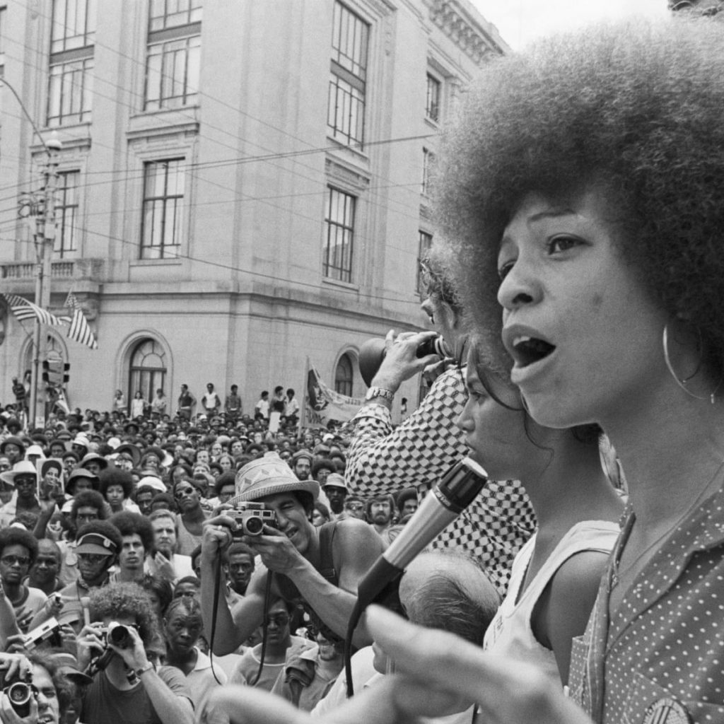 A black and white photograph of Angela Davis (right hand side) speaking to a large, assembled crowd into a microphone.