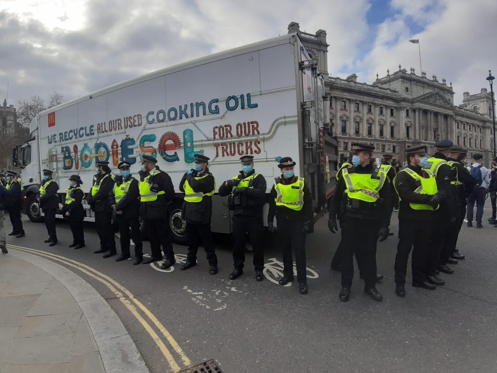 Police protecting a McDonald's lorry in London on Saturday