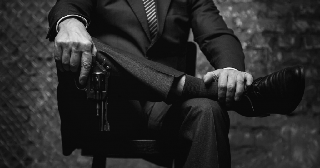 A shadowy figure in a suit holds a gun while sitting on a chair
