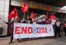 Crowd of strikers with End Fire & Rehire banner