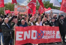 Crowd with flags and 'end fire and rehire' banner