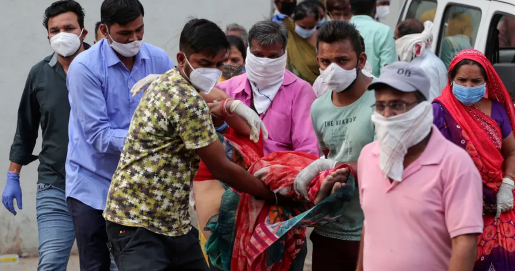 Relatives carry a woman who fainted after seeing the body of her husband at a hospital in Ahmedabad, India