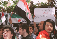 Protestor holds a Palestinian flag at a demonstration in Syria in 2011.