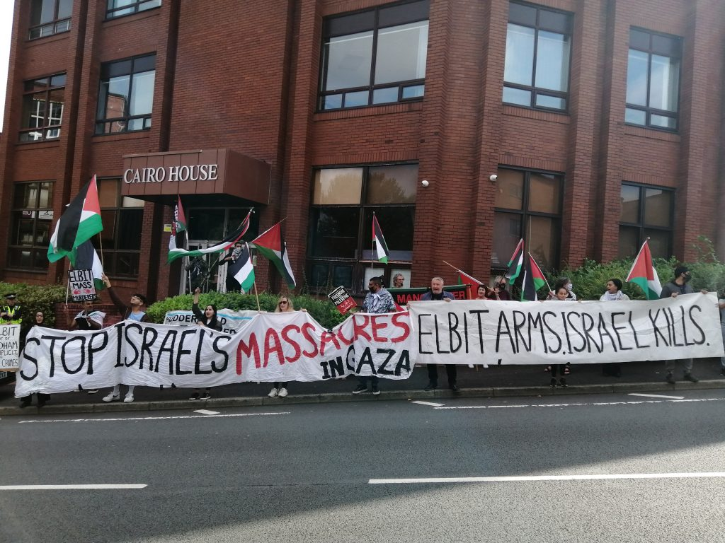 Protestors ouside cairo house hold banners along roadside. Banners read 'Stop Israel's Massacres in Gaza'; 'Elbit Arms, Israel Kills'