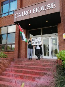 Protestors satand outside the doorway of Cairo House, which is stained with red paint. Placard reads 'Elbit out of Oldham'
