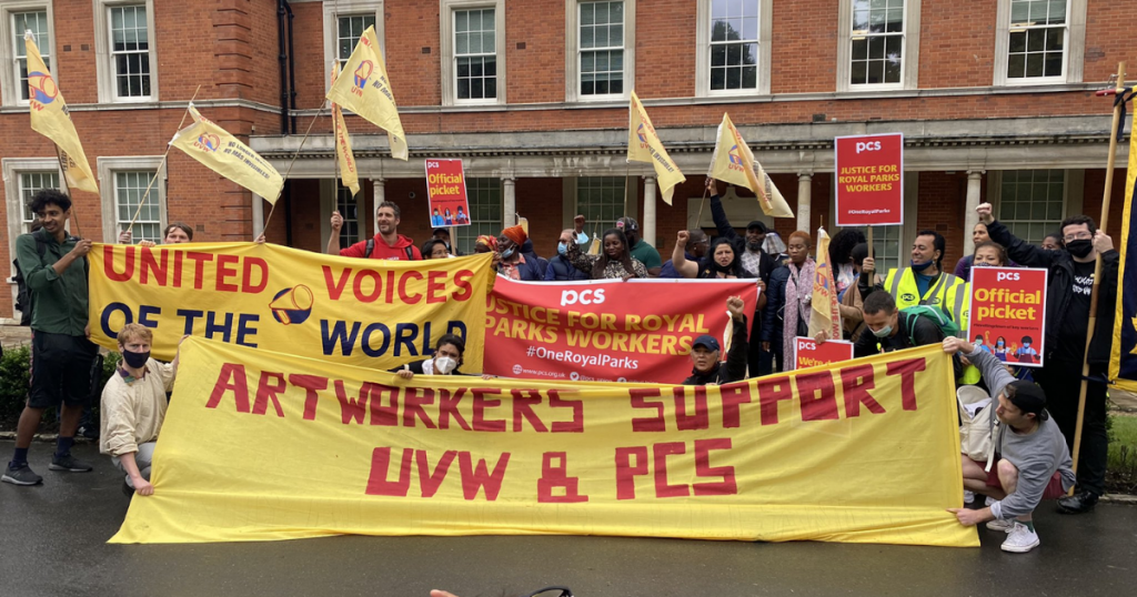 Strikers and supporters in the Royal Parks industrial dispute hold banners and flags representing the unions UVW and PCS, and a large banner that reads 'Art workers support UVW & PCS'