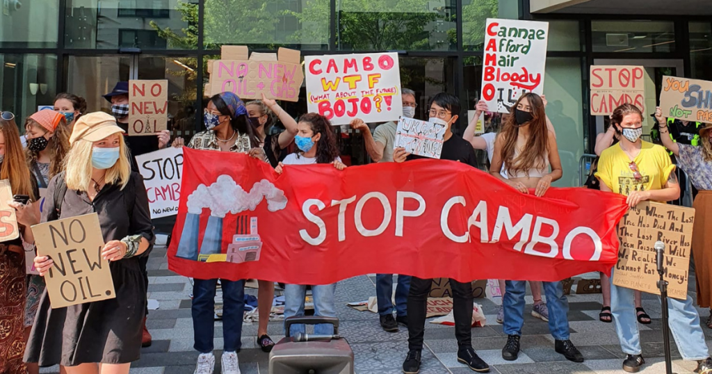 Protestors at a rally against developing the Cambo oil field, holding placards and a banner reading 'stop cambo'