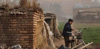 Image from Liang Village, a woman pulls a trolley next to brick.