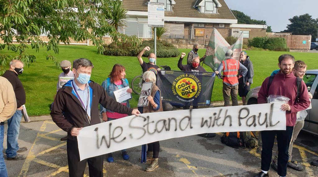 Protestors in support of Paul Holmes. Banner reads 'We stand with Paul'