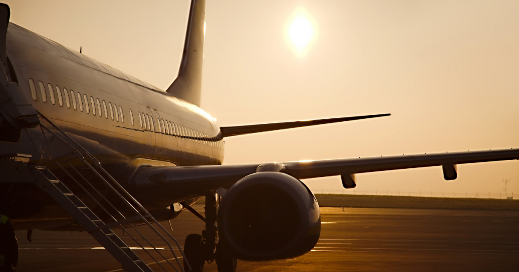 A jet sits on a dry runway with the sun overhead.